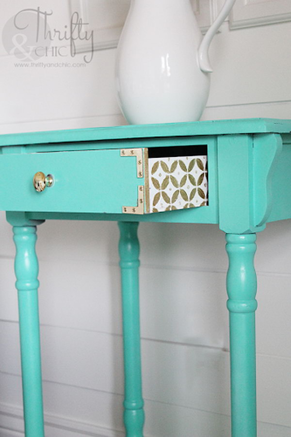 A cute design on the drawer with some gold and white paint.