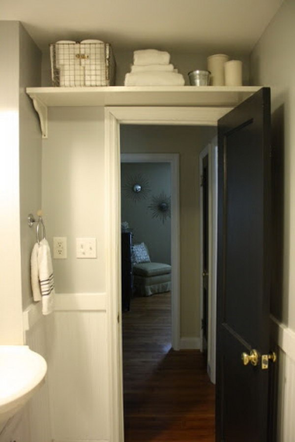 To maximize space in the bathroom add a shelf over the door to store extras like toilet paper and extra towels.