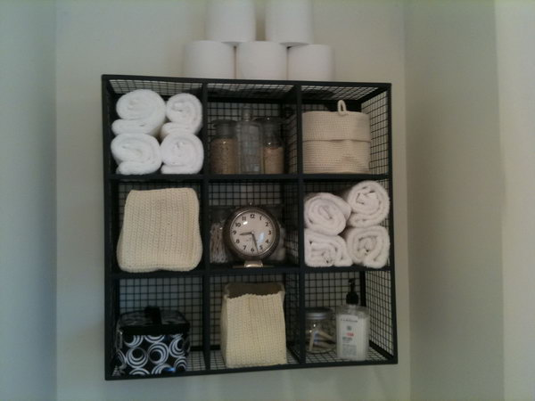 With very limited storage above the toilet , this wire cube storage idea makes functional display.