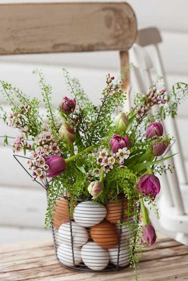 Easter Centerpiece with Eggs and Flowers. Place flowers in a vase inside wire basket and arrange plastic eggs in between. It's perfect for an elegant Easter table display.