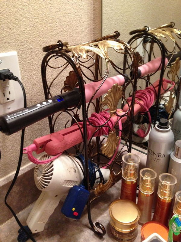 Wine Rack Hair Dryer Holder. Use a small and decorative wine rack to store your hair tools. It helps in keeping the bathroom counters clean and beautiful.