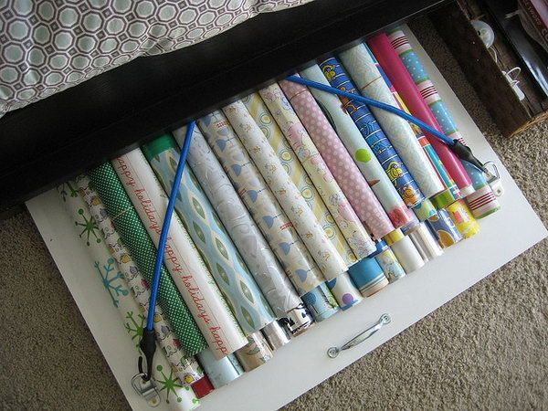 Organize your wrapping paper under bed with a board with bungee cords. Keep it smooth and clean so you will not have to buy new gift wrap every time you wrap a present.