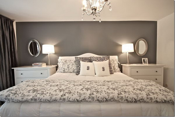 This master bedroom looks very nice, big and tall with a dark gray accent wall and the practical chests instead of small nightstands.