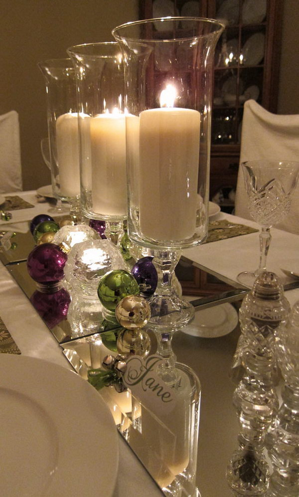 Mirror as a table runner. Look at this amazing table with jingle bells and candles on. It also features the mirror as the runner of the table. It looks super pretty with the candle light reflected by the mirror.