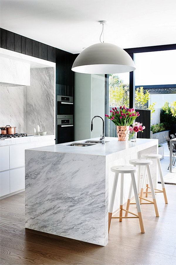 Stylish black and white kitchen. In this kitchen, the black and white contrast has been maintained throughout the décor, including the marble waterfall countertop. The light fixture and the custom made stools infuse this kitchen with a stand-out sense of stylish and glamour.