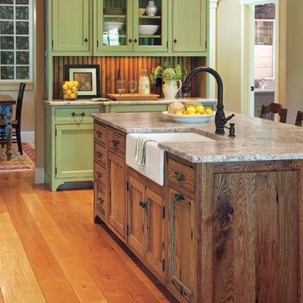 Old country farm look kitchen. The vintage wood tone island add a farm look to this green kitchen. And the black sink on the top would really make island colors flow.