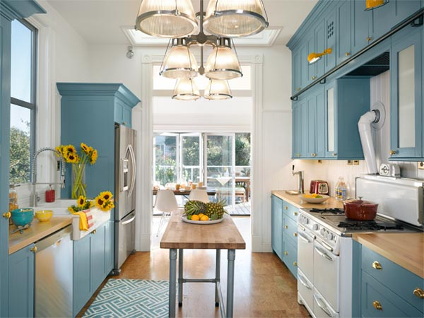 Bright kitchen. Opened up to the sun, the galley kitchen is now blue and white and bright all over, with an existing vintage Wedgewood stove as its centerpiece.
