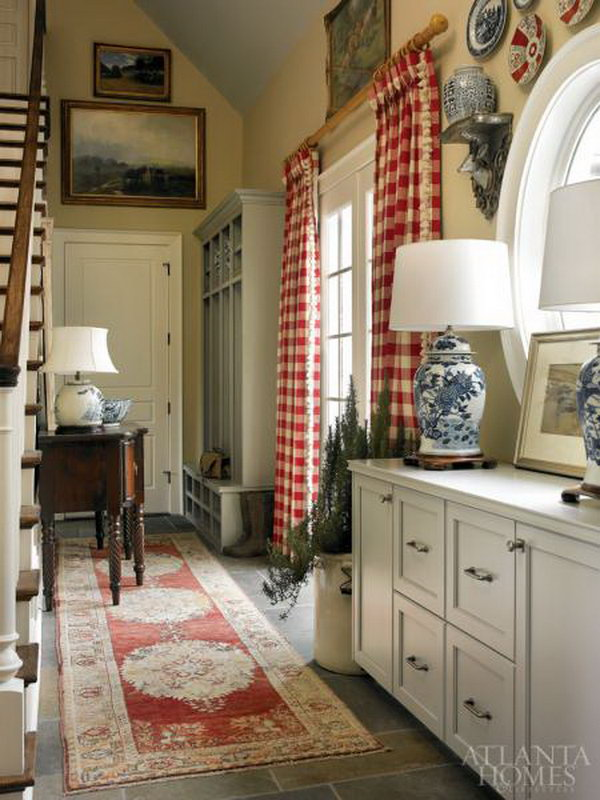 Farmhouse mud room. Classic blue-and-white relics ecco other traditional decors like an Oushak rug, mahogany buffet and red-and-white check curtains.  And the open storage area features hunting gear belonging to the designer's family and friends.