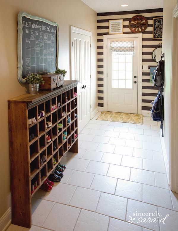 Rustic shoe presentation. This is a functional mud room, with stripe wallpaper, vintage shoe cabinet, chalkboard, white doors. The Designer creatively added the strips and made the chalkboard calendar from an old mirror. And this infuses rustic look to this stylish space.