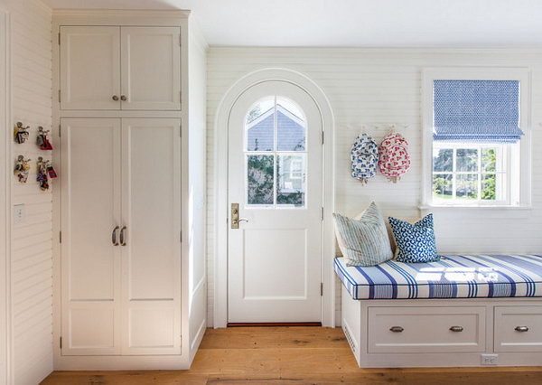 Mediterranean style mudroom with coastal decor. What a cute and functional mud room! The lovely coastal decor complements the classic architectural details.