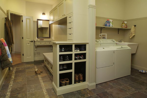 Gray colored mudroom. This nice mudroom gives a place to keep the mud out. With easy-to-clean floors, plenty of shoe storage below the bench, lots of hooks and even some spacious cabinets, this mudroom is really functional.