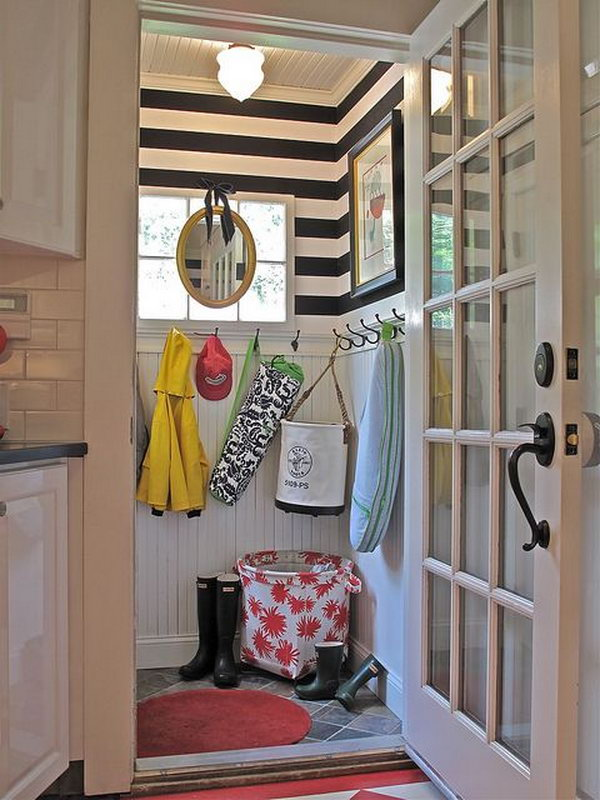 Small neat mudroom. Such a cool tiny mudroom with a great use of the space and every detail in the room is lovely. Like the white door, the panel board wall treatment. And the black hooks, stripe wallpaper, big handle add stylish to the space. Usually, mudrooms are dirty and scuffed and full of old, rotting rain jackets and boots. But this one is incredibly neat.