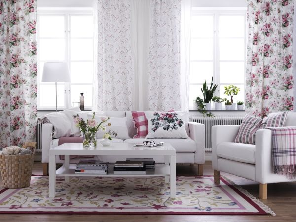 Soft and Feminine IKEA Living Room. White earthy neutrals and updated versions of florals gives this living space a fresh and feminine feel. White and soft sofas, white coffee table really work with the floral and beautiful curtains.