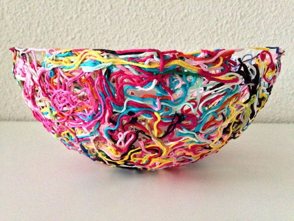 Colorful Yarn Bowl. Never throw away leftover bits and pieces from yarn projects because you can make a piece of art for your home decor. Tutorial via