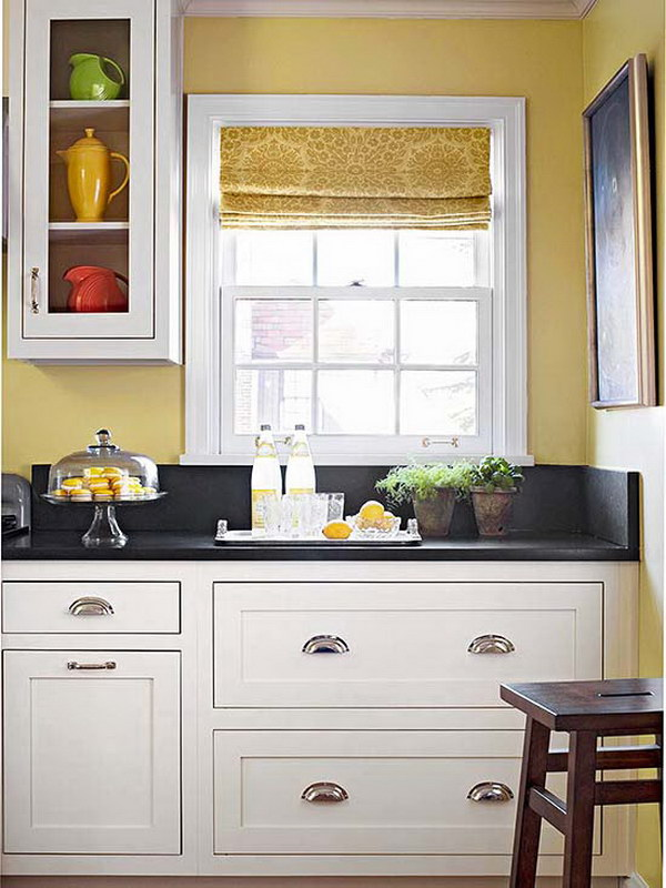 Crisp White Cabinets Paired with Dark stone countertops and Warm Yellow Wall Color.