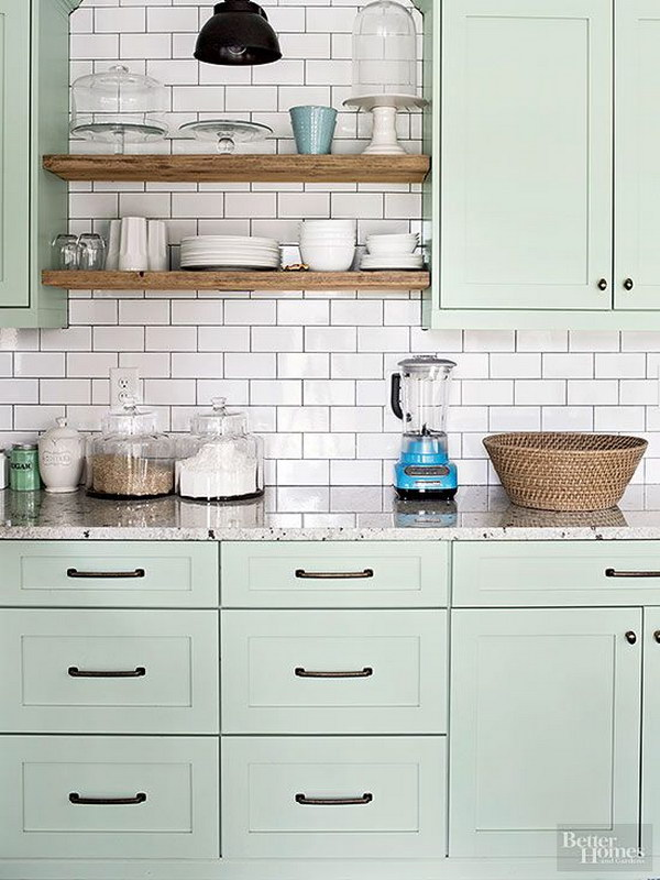 Light Green Painted Kitchen Cabinets with Shiny White Subway Tile Backsplash.