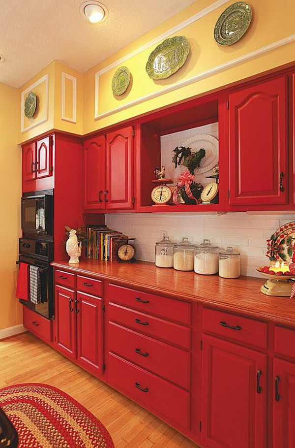 Red Cabinets paired with Pale Yellow Walls and White Subway Tile Backspalsh.